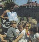 Our teacher reads to the Morning Group of kindergarten children, outside in the kindergarten grounds, in 1961